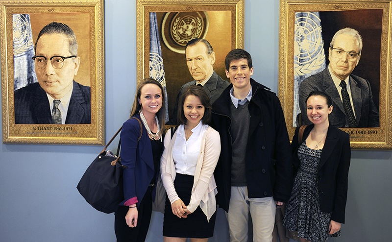 Adelphi students pose in front of portraits at the UN