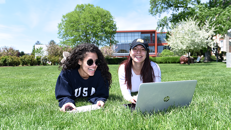 Two Adelphi students use a laptop on the lawn