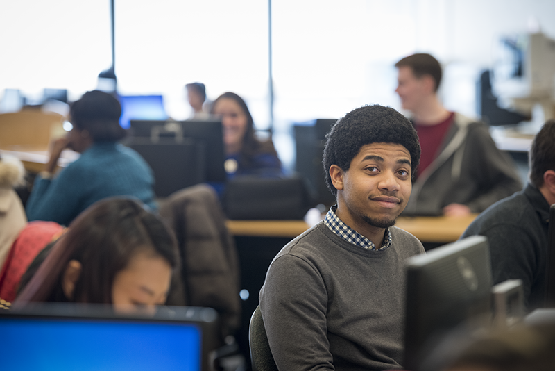 Adelphi student in a computer lab smiling