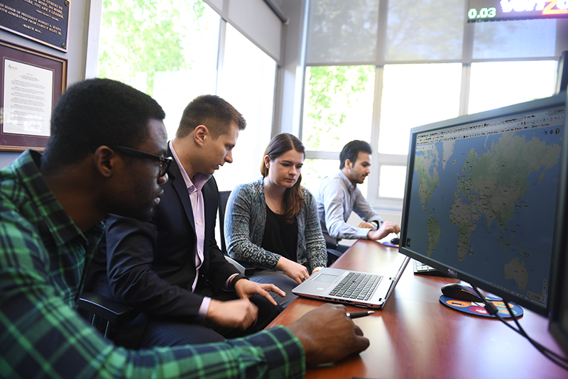 Adelphi students look at a map in the trading room