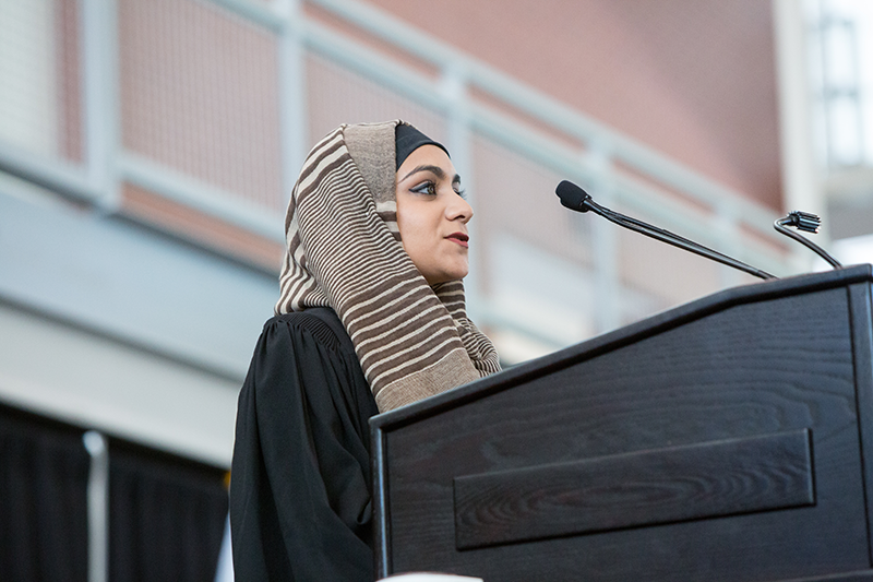 Female Adelphi student at podium delivering an impassioned speech