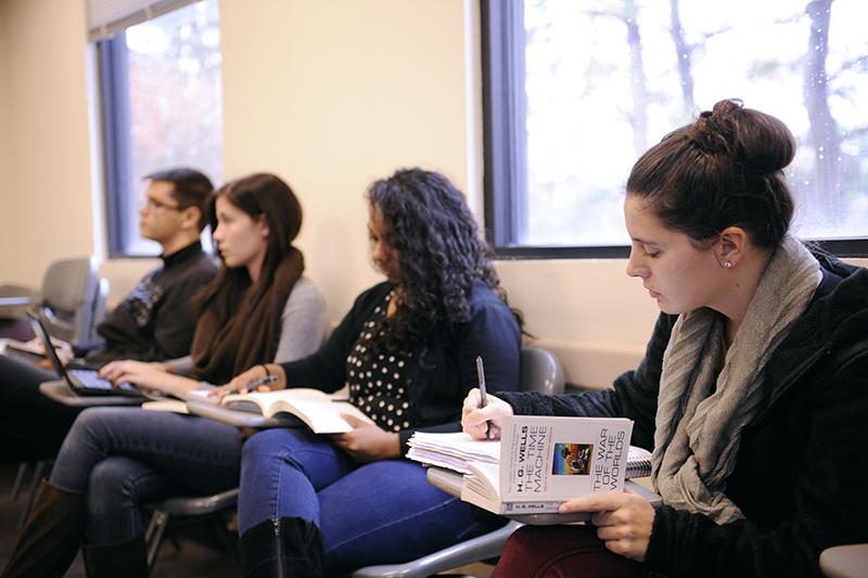 Adelphi english students writing notes while holding a novel