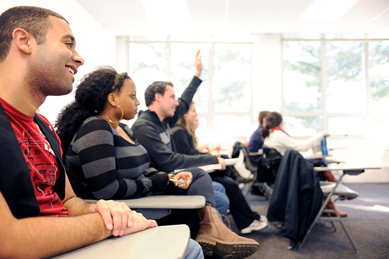 Diverse group of Adelphi students smile during class