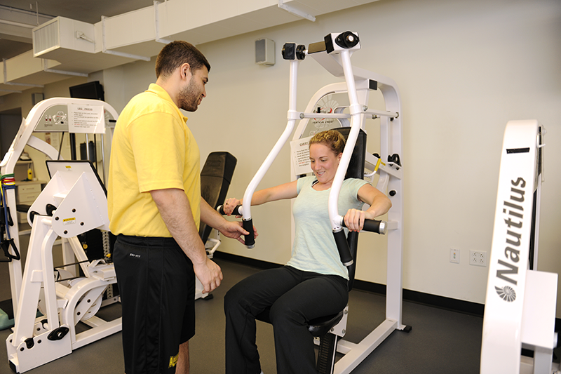 Exercise Science student with an athlete using a piece of equipment