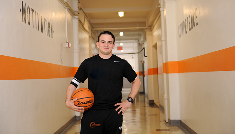 Student holding a basketball in a hallway