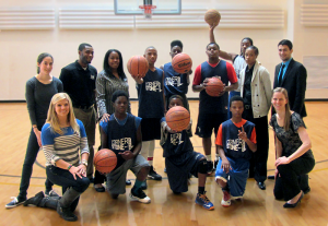 Professor Whitley with youth in the Adelphi Gym holding basketballs