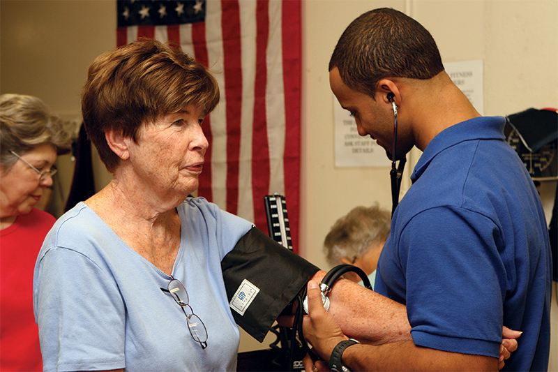 Taking blood pressure of a woman in the adult fitness program