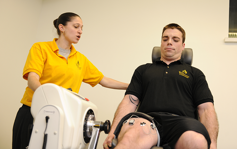 Trainer helps athlete on elliptical