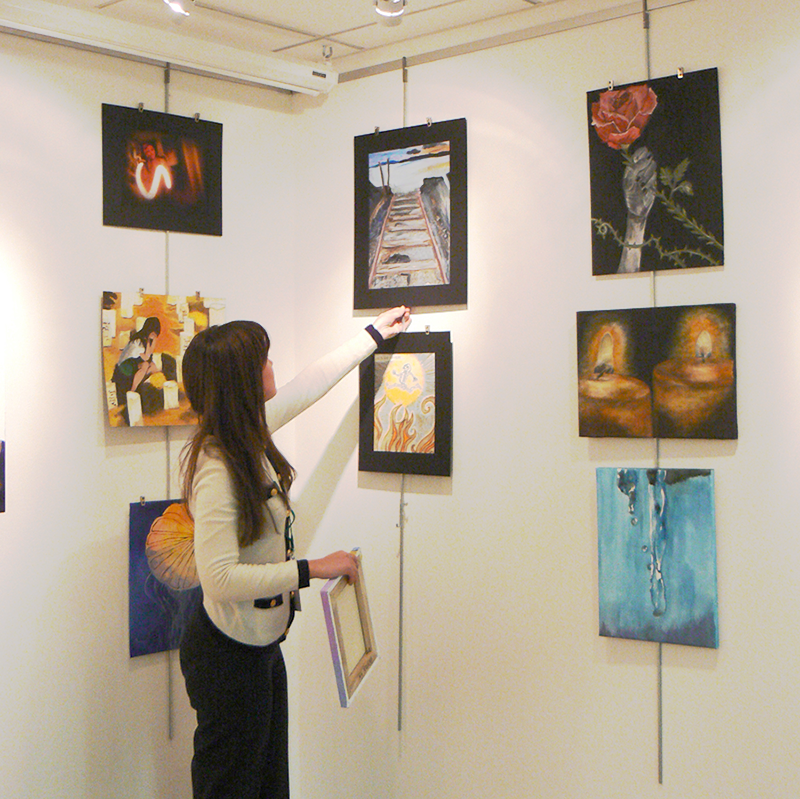 Art student hanging work on the wall of an exhibition