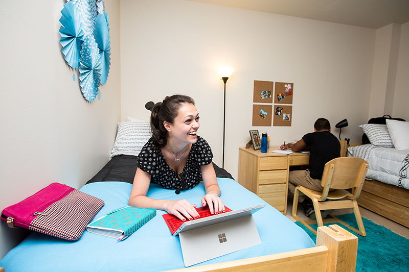 Dorm room interior with student on the bed