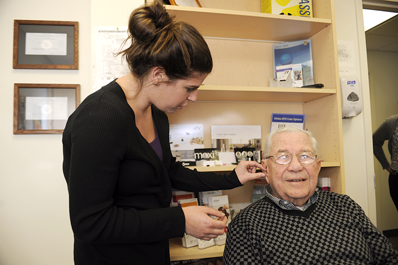 AuD student fitting a hearing aid