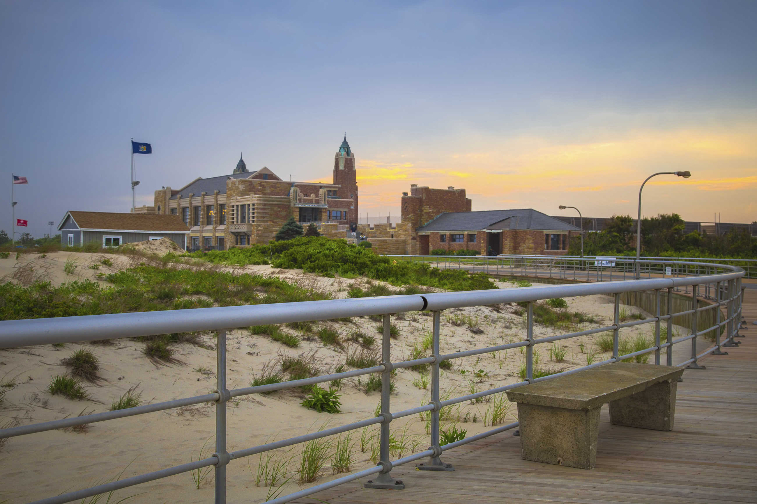 Sunset over boardwalk and bathhouse at historic Jones Beach State Park. This Long Island landmark commissioned by Robert Moses opened to the public in 1929.