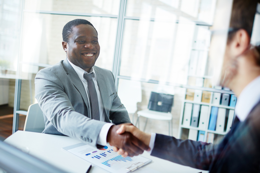 African American and Caucasian professionals shaking hands