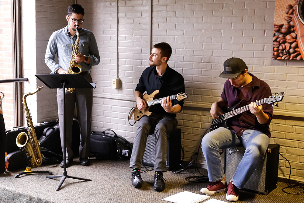 Two Adelphi students with guitars and one with a saxophone play music together in the Ruth S. Harley University Center Underground Cafe.