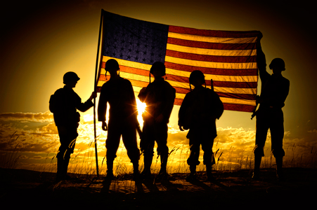 Silhouetted soldiers at sunset