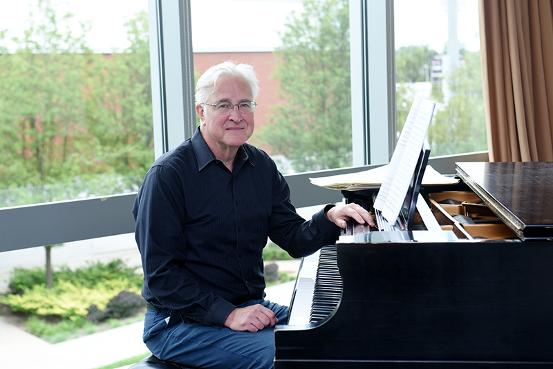 Professor of Music Paul Moravec seated at a piano.