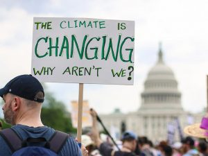 "A man holding a sign that says ""the climate is changing, why aren't we?"""