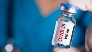 Person holding a cOVID-19 vaccine vial