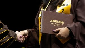 An Adelphi graduate shakes hands while holding her diploma.