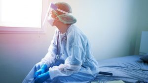 A nurse in PPE sitting on a bed and looking out a window.