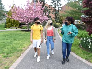 Students walking on campus wearing masks and being safe together.