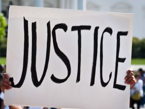 """A protest sign that states the word """"Justice"""" boldly."""