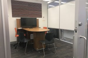 A peek inside a collaboration studio pod, showing a screen, deak and seating for group study