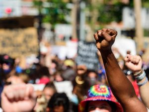 A photo of a racial equality protest focused on the upraised fists. Signs and people are blurred in the background.
