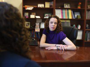 Professor Katherine Fiori, PhD sitting at her desk.