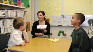 An Adelphi student working with two school aged children on reading and speech skills with flash cards.