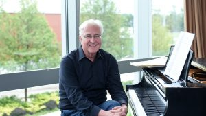 University Professor Paul Moravec, DMA pictured in front of a piano on Adelphi University's campus.
