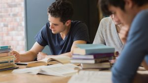 Students at a desk studying with books around.