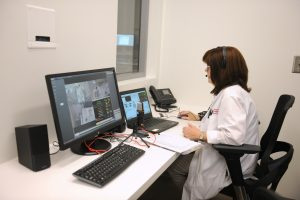 During a high-fidelity simulation, a faculty member provides remote support to nursing students to guide them through a variety of clinical scenarios.