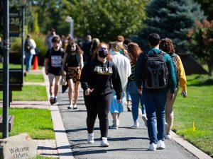 Students walking on the campus pathways wearing masks and Adelphi University sweatshirts.